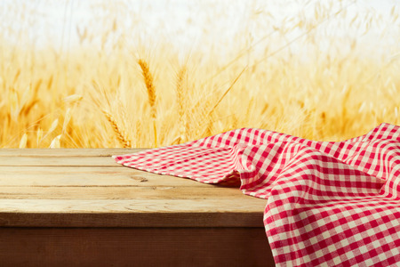 Red checked tablecloth on wooden deck table over wheat field background Stock Photo