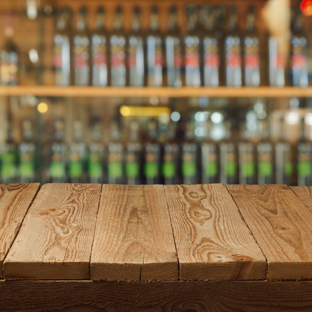 wine store: Empty wooden table over wine store background Stock Photo