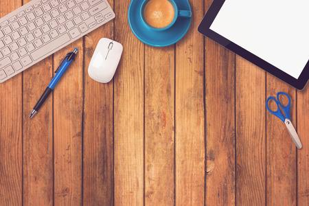 オフィスの机のモックアップをタブレット、キーボード、木製の背景にコーヒーとテンプレート