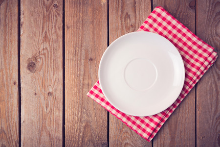 empty table: Plate on checked tablecloth over wooden background. View from above Stock Photo