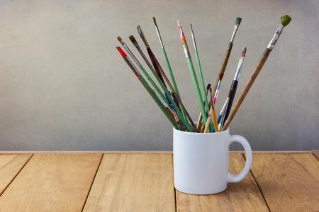 Brosses de peinture à tasse blanche sur la table en bois