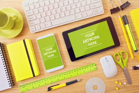 website template: Smart phone and tablet mock up template on office desk Stock Photo