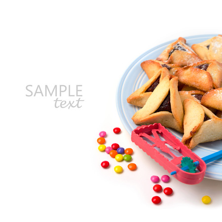 holiday maker: Hamantaschen cookies on plate and grogger on white background