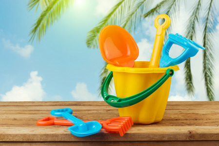 bucket and spade: Children bucket and spade on wooden table over palm tree background Stock Photo