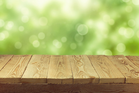 Empty wooden deck table with foliage bokeh background