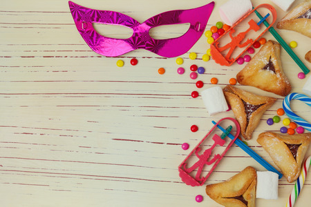 Background for Jewish holiday Purim with mask and hamantaschen cookies