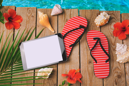 sandal tree: Digital tablet, flip flops and hibiscus flowers on wooden background. Summer holiday vacation concept. View from above
