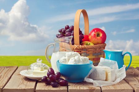 牛乳、カッテージ チーズ、バター、草原の背景の上のフルーツ バスケット 写真素材