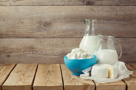 milk jugs: Cottage cheese and milk bottle over wooden background