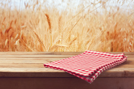 Tablecloth on wooden table over wheat field