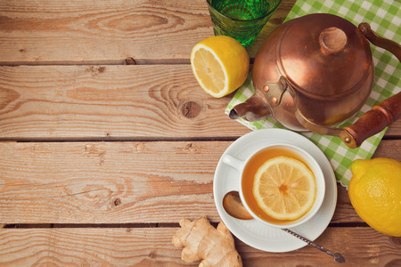 Cup of tea with ginger, lemon and tea pot on wooden table. View from above
