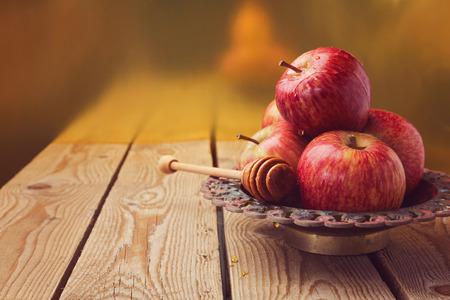 リンゴとお祝いロッシュ hashana (新しい年) ユダヤ人のための木製のテーブルの上に蜂蜜