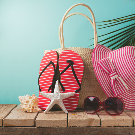 seashore: Flip flops and summer bag on wooden table
