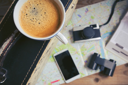 maleta: concepto de planificación de viajes con la taza de café y una maleta. Centrarse en la frontera de la taza de café