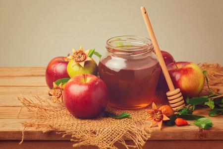 honey apple: Honey, apple and pomegranate on wooden table. Retro filter effect