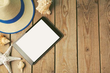 デジタル タブレット、夏帽子そして木製の背景で貝殻