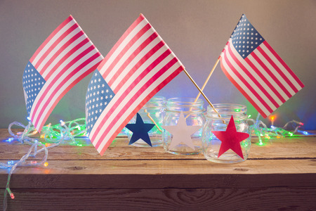 independence day: 4th of July celebration with USA flags in glass jars on wooden table