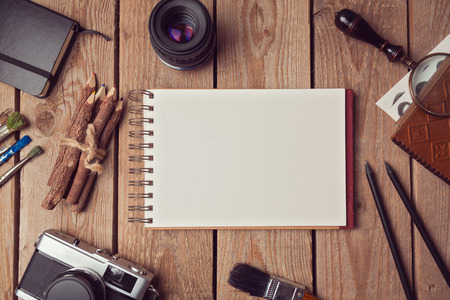 Notebook bespotten voor kunstwerk of ontwerp presentatie met film camera en lens. Uitzicht van boven