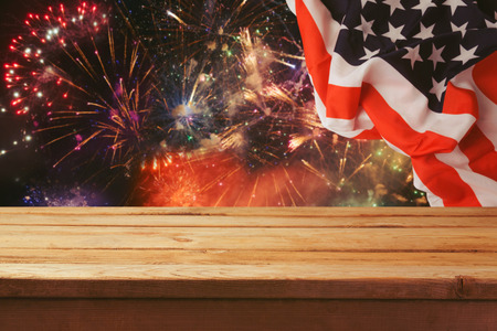 stars and stripes background: 4th of July background on Wooden table over fireworks and USA flag