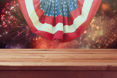 Wooden table over fireworks. 4th of July background of Independence day celebration