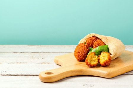 Falafel balls served with pita and lettuce on a wooden board Stock Photo