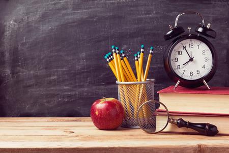 教育: 回到學校背景的書籍和鬧鐘在黑板