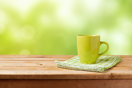 beverage display: Coffee cup on wooden table over green bokeh background. Mock up for design display Stock Photo