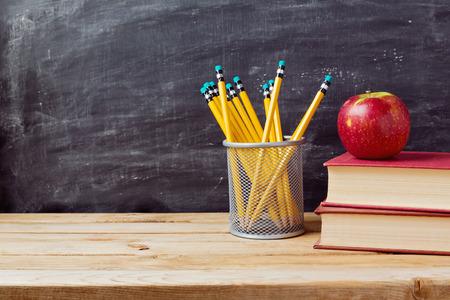 in the back: Volver a la escuela de fondo con libros, l�pices y manzana sobre pizarra Foto de archivo