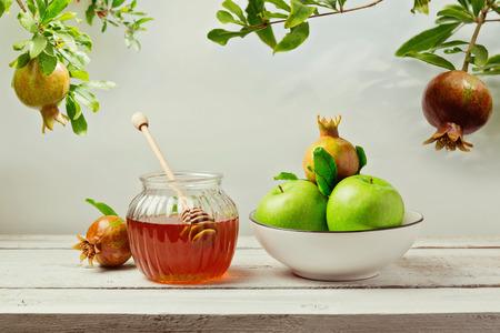 Jewish holiday Rosh Hashana (new year) background with honey jar, apples and pomegranate tree Foto de archivo