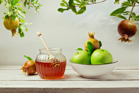Jewish holiday Rosh Hashana (new year) background with honey jar, apples and pomegranate tree 免版税图像