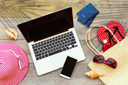 Laptop computer and smart phone with beach accessories on wooden board Stok Fotoğraf