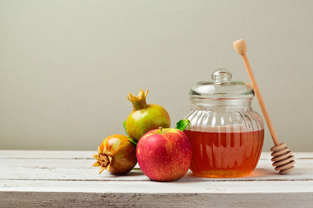Honey jar, red apples and pomegranate on white wooden board Banque d'images