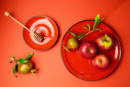 a pomegranate: Apples and pomegranate on red background. View from above Stock Photo