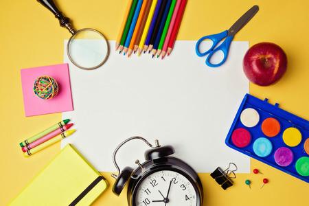 material escolar: Volver a la escuela de fondo con papel y útiles escolares blancas en blanco. Vista desde arriba
