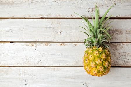 木の板にパイナップルと夏の背景