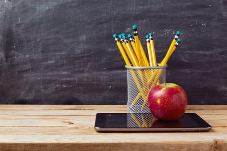 maestra: De nuevo a fondo de la escuela con la tableta, l�pices y manzana sobre pizarra Foto de archivo