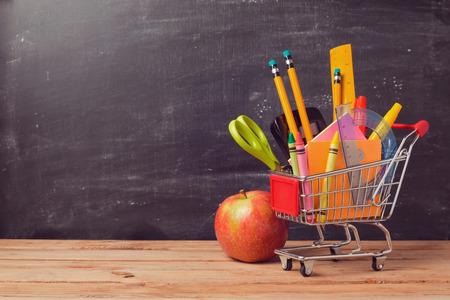 Nákupní košík s školní pomůcky přes tabuli pozadí