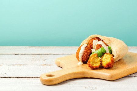 fried: Falafel balls in pita with tahini sauce on wooden board