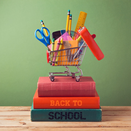 Back to school concept with shopping cart on books Stock Photo