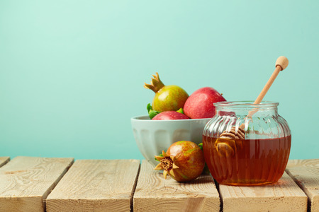 Honey jar and pomegranate on wooden table with copy space