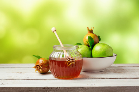 honey jar: Honey jar and fresh apples with pomegranate over green bokeh background Stock Photo