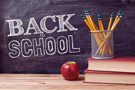 school book: Back to school lettering with books, pencils and apple over chalkboard background Stock Photo