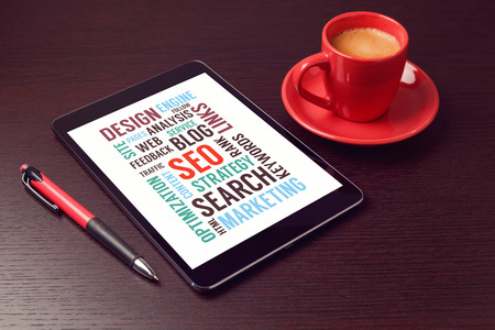 seo optimization: Digital tablet with SEO words and coffee cup on office desk Stock Photo