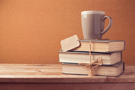 written: Old vintage books with cup and price tag on wooden table. Back to school concept Stock Photo