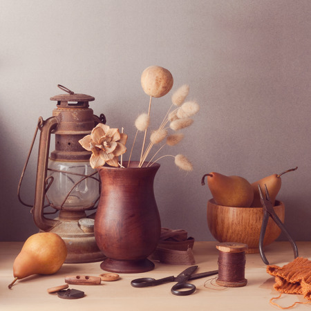 vase of flowers: Dry flowers and pears on wooden table. Rustic still life