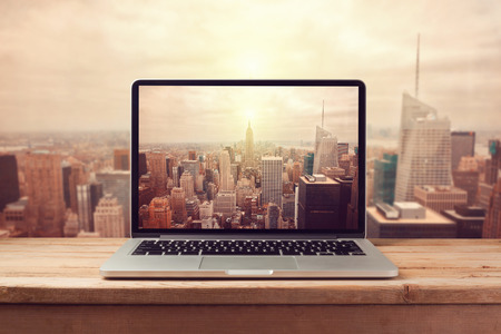 Laptop computer over New York city skyline. Retro filter effect