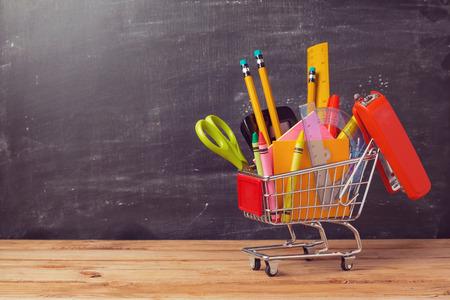 scuola: Carrello della spesa con materiale scolastico su sfondo lavagna. Ritorno a scuola concetto di vendita