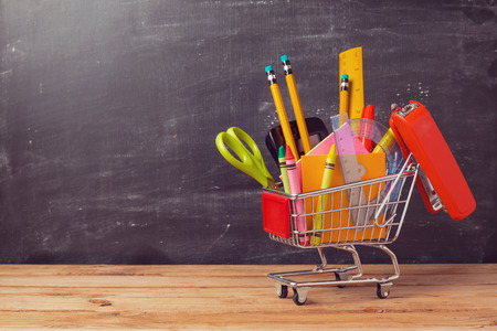 back to school supplies: Shopping cart with school supplies over chalkboard background. Back to school sale concept