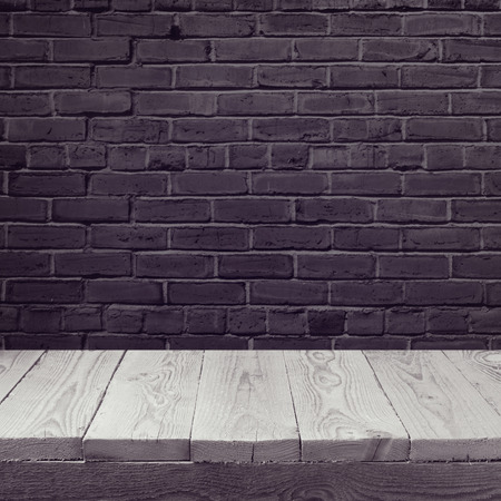 brick wall: Empty wooden board background over black brick wall