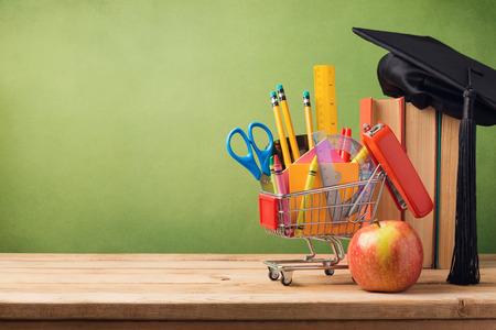 koncepció: Vissza az iskolába koncepció bevásárlókosár, könyvek és érettségi kalap Stock fotó